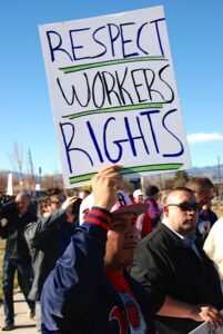 """Man holds a sign at a rally that says """"respect workers' rights"""""""